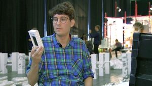 Muotoilija Kasper Strömman tarkastelemassa Legoista rakentamaansa kännykkäkoteloa.
