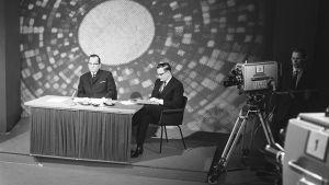 Pääministeri Ahti Karjalainen istuu pöydän takana. Oikealla kaksi televisiokameraa.