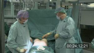 Kaksi lääkäriä potilaan vierellä leikkaussalissa.
