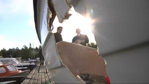 Reikä veneen kyljessä Vaasan Isolahden pienvenesatamassa syysmyrskyn jälkeisessä aamuauringossa.