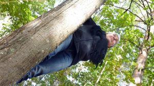 Valokuvataiteilija Maria Kärkkäinen kiipeilee puussa.