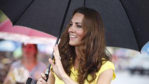 Herttuatar Catherine vilkuttaa sateenvarjon alta.