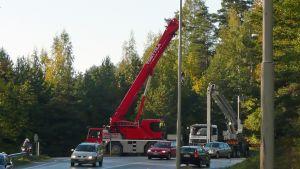Nosturit nostavat liikenneopasteita erikoiskuljetuksen tieltä.