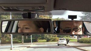 Autokoulun oppilaan ja opettajan silmät näkyvät taustapeileistä.