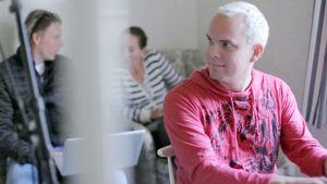 Jaakko Salovaara käyttää kannettavaa tietokonetta, taustalla on kaksi musiikkileirille osallistunutta artistia.