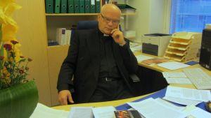 Kari Koivu mietteliäänä työpöytänsä ääressä, viimeinen saarna levällään