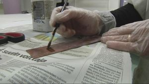 Nainen sivelee pensselillä metallisuikaletta.