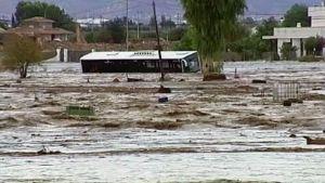 Erilaista rojua kelluu tulvavedessä sen saartaman linja-auton ohitse.