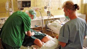 Virolainen lääkäri tutkii potilasta. Sairaanhoitaja takana oikealla.