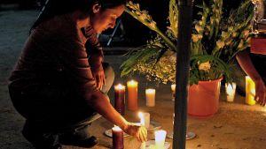 Nainen asettaa kynttilää palamaan kadulle.