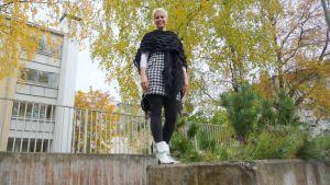 Vaalea nainen seisoo kerrostalonpihan betoniaidalla.