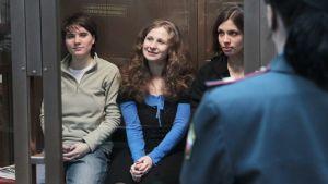 Pussy Riotin jäsenet istuvat lasin takana.