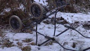 Kaadetut lastenvaunut lumisessa maassa.