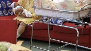Äiti pitelee vastasyntynyttä vauvaansa sylissään.