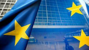 EU:n lippu heiluu Euroopan Unionin rakennusten edessä Brysselissä. Lipun läpi näkyy matkalaukkua vetävä mies.