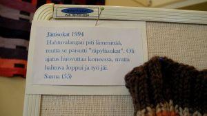 Teksti käsityönäyttelyssä, joka kertoo miksi sukat jäivät aikanaa keskeneräisiksi.