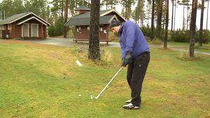 Mies lyö golfpalloa Oulun Sankivaarassa.