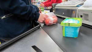 Margariinipaketti ja tomaattipussi kaupan kassan liukuhihnalla.