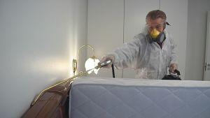Tuholaistorjuja suihkuttaa myrkkyä sängyn taakse