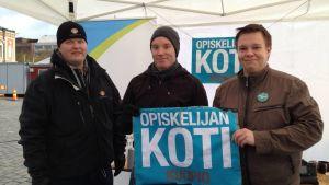 """Opiskelijat pitävät käsissään kylttiä, jossa lukee """"Opiskelijan koti, Kuopio""""."""