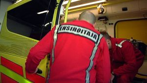 Ensihoitajia nousee ambulanssiin.