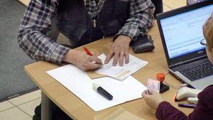 äänestäjä allekirjoittaa äänestyskupongin