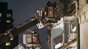 Palomiehet tutkivat Sandy-myrskyn tuhoamaa taloa New Yorkissa maanantaina.