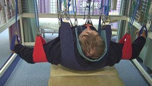 Mies lepää selällään köysien varassa suspensiohoidossa.