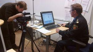 Mediatoimittaja kuvaa tietokoneella työskentelevää Tampereen aluepelastuslaitoksen tiedotuspäällikkö Veijo Kajania