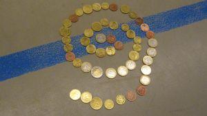 Euroja lattialla spiraalimuodostelmassa