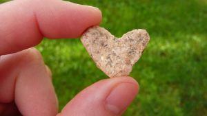 Sydämen muotoinen kivi etusormen ja peukalon välissä.