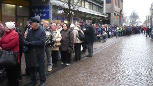 Ihmisiä pitkässä jonossa Hämeenlinnan kävelykadulla.