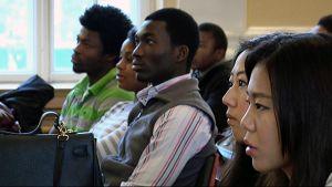 Nuoria opiskelijoita eri maista kuuntelemassa seminaarissa.