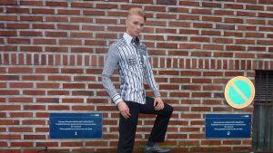 Lahtelainen Christian Patrikainen poseeraa tiiliseinän edessä.