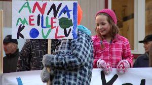 Oppilaalla kädessä banderolli Nyrölän koulun pihalla.