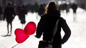 Nainen kantaa sydämen muotoisia ilmapalloja kadulla.