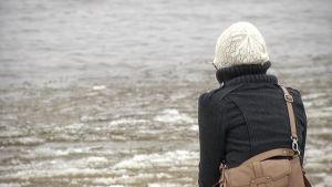 Nainen istuu rannalla