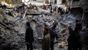 Miehiä seisomassa pommin jättämän kuopan reunalla.