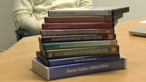 Viittomakielelle käännetyt kirkolliset tekstit pöydällä pinossa: 1 VHS- ja 8 DVD-koteloa.