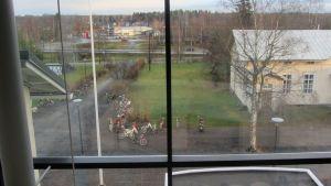 Kuvassa ikkunasta näkyy pihalle, jossa on polkupyöriä ja ruohikkoa
