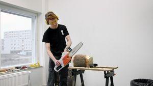 Kuvanveistäjä Paula Salmela työstää materiaalia moottorisahalla Porvoon taidetehtaalla.