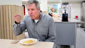 Hannu Moilanen syö ruokaa koulun keittiössä, takana keittiöhenkilökuntaa ja ruokapiste.
