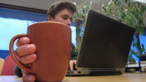Mies käyttää tietokonetta kahvikuppi kädessä