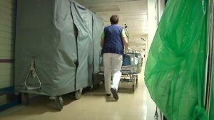 Kuvassa hoitaja työntää potilasvuodetta ahtaalla ja tavaroita täynnä olevalla käytävällä