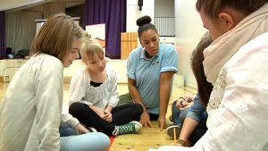 Walter ry:n projektikoordinaattori keskustelee Donnerin koulun neljän oppilaan kanssa liiikuntasalissa.