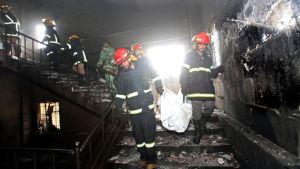 Pelastustyöntekijät kantavat ruumista ulos palaneesta tehtaasta Bangladeshissa.