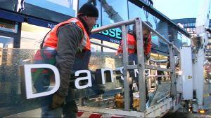 Rakennusmiehet kantavat Danske Bankin kylttiä.