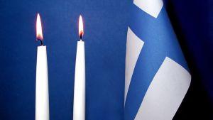 Kaksi kynttilää ja Suomen lippu.