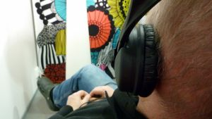 Mies kuuntelee musiikkia kuulokkeilla.
