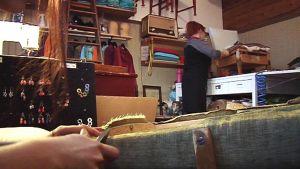 Verhoilija seisoo selin kuvaan, jonka etualalla toinen käistyöläinen leikkaa verhoilukangasta.